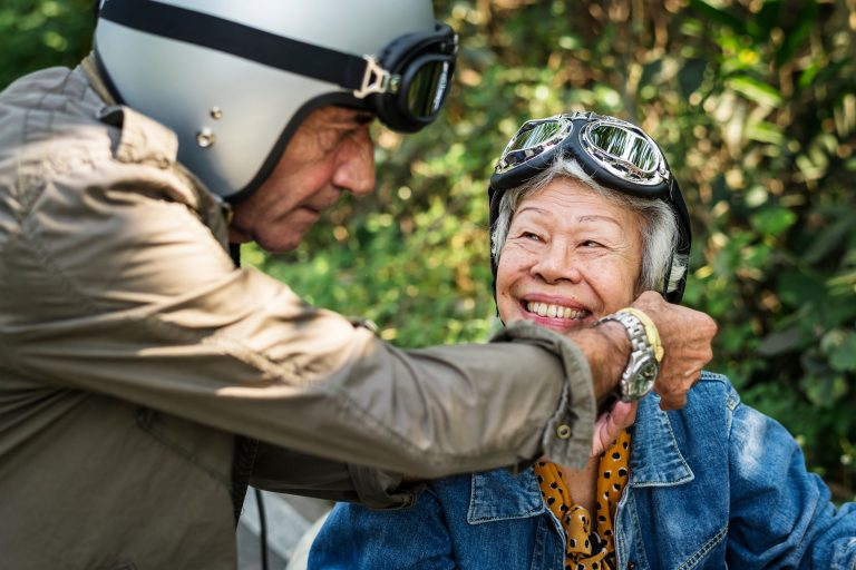 Elderly lady smiling towards the camera wearing a motorcycle helmet and goggles