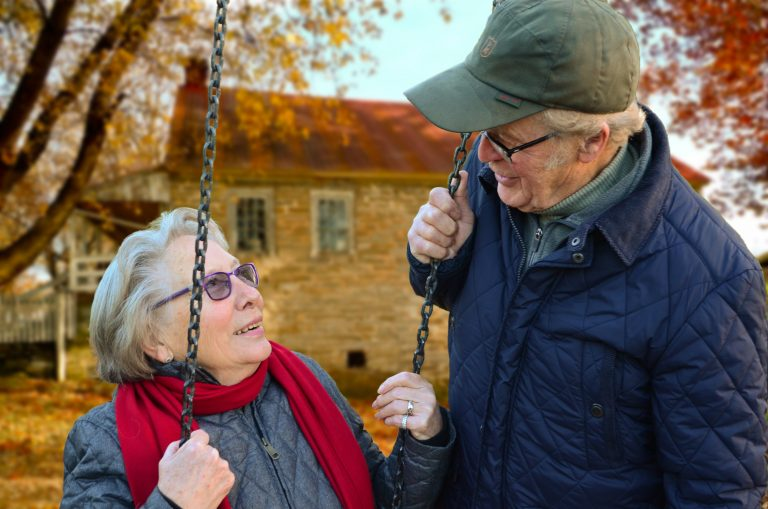 Elderly lady sat on a swing looking at an elderly man holding the rope