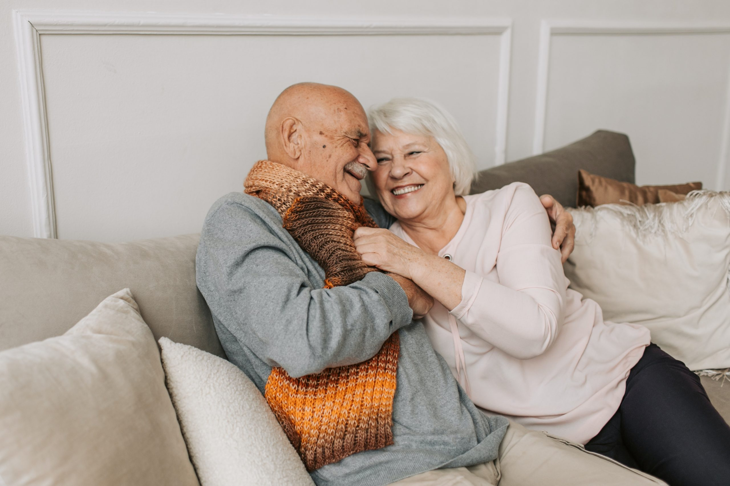 Elderly couple sat smiling and cuddling on a sofa