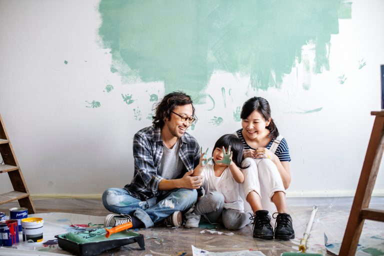 Family sat on the floor with paint on their hands and painted hand prints on the wall behind them