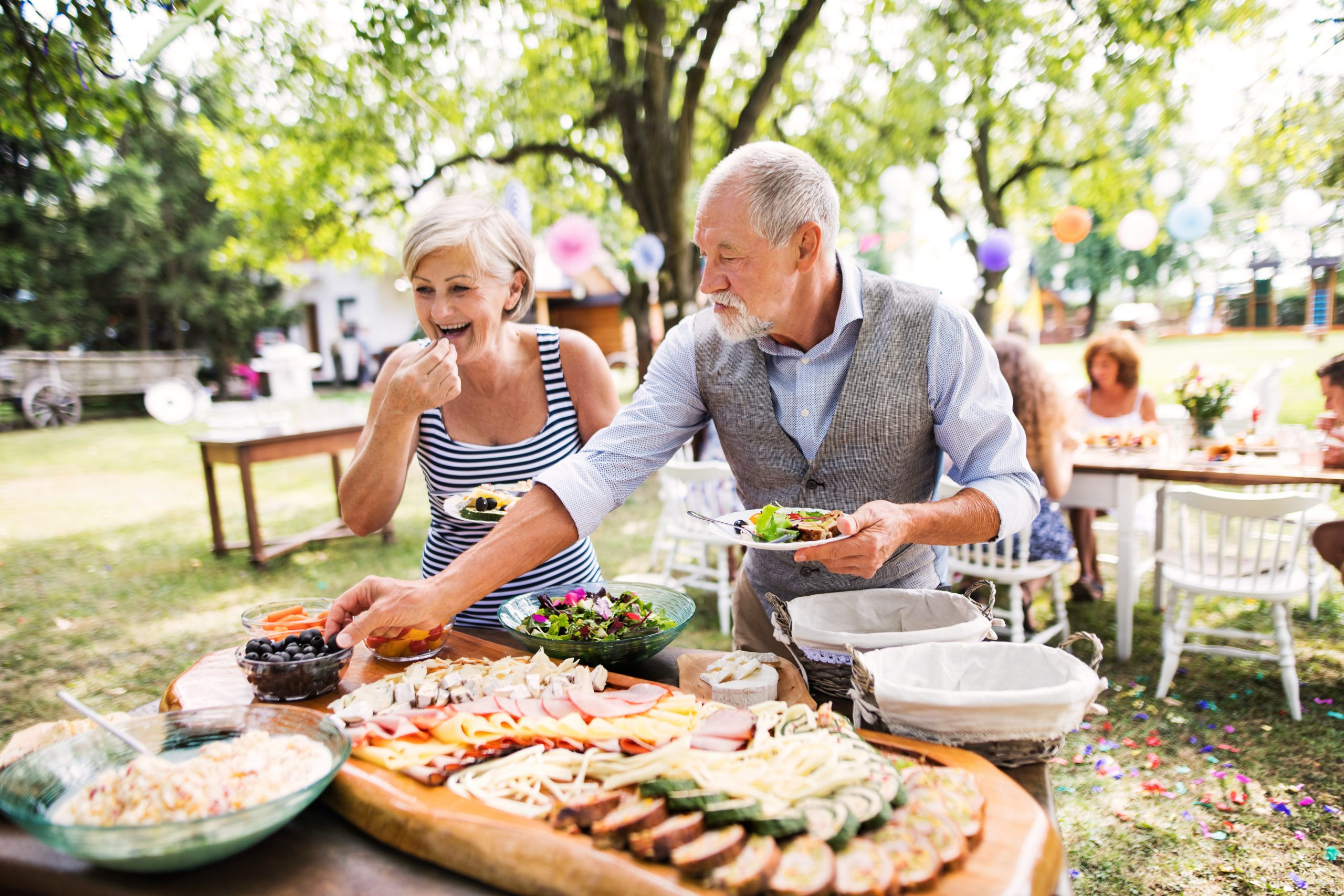 Elderly couple smiling and eating from a buffet table outside