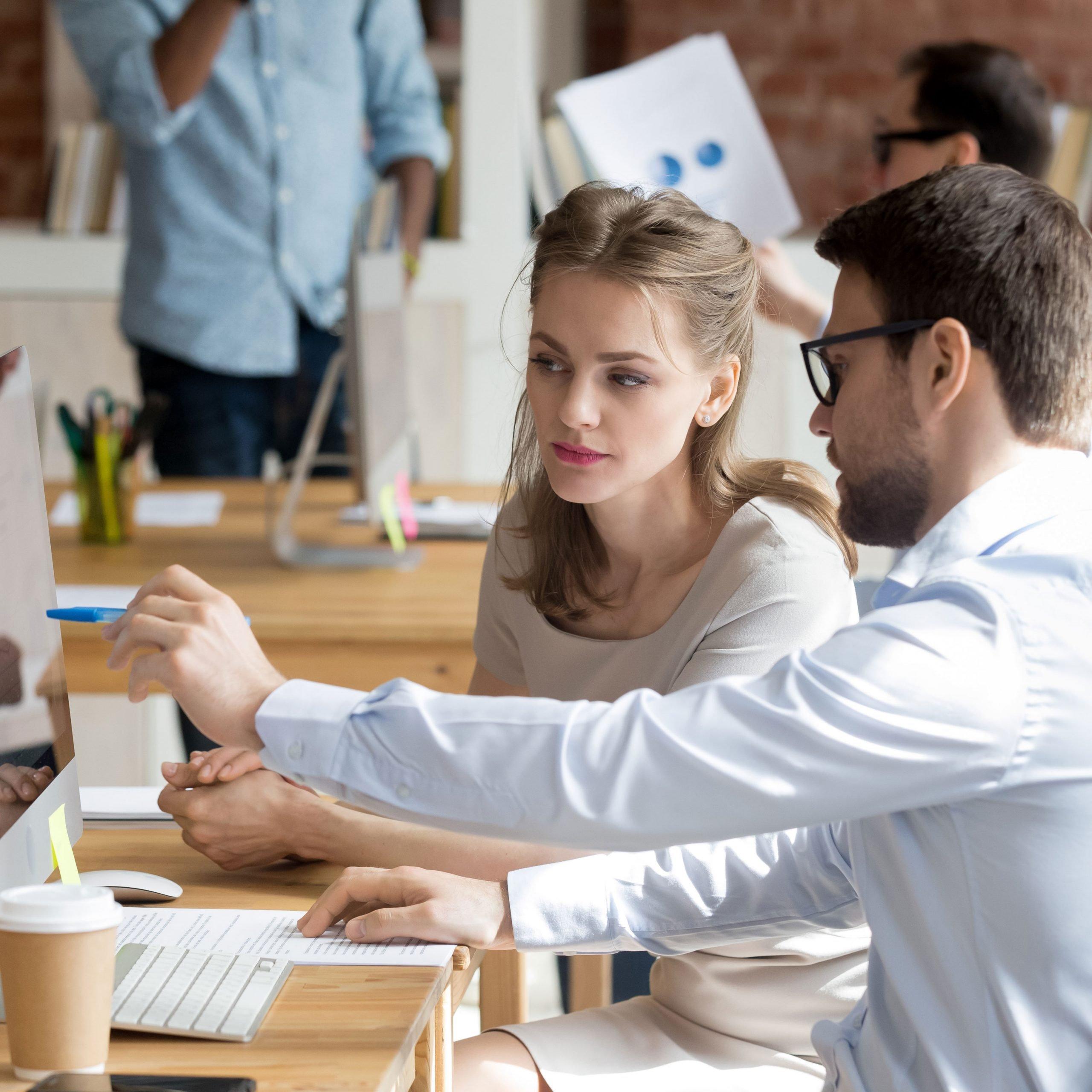 Woman and man sat at a desk looking at a computer screen