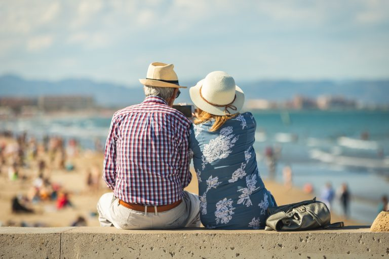 Couple sat on a wall looking out at the beach on a sunny day
