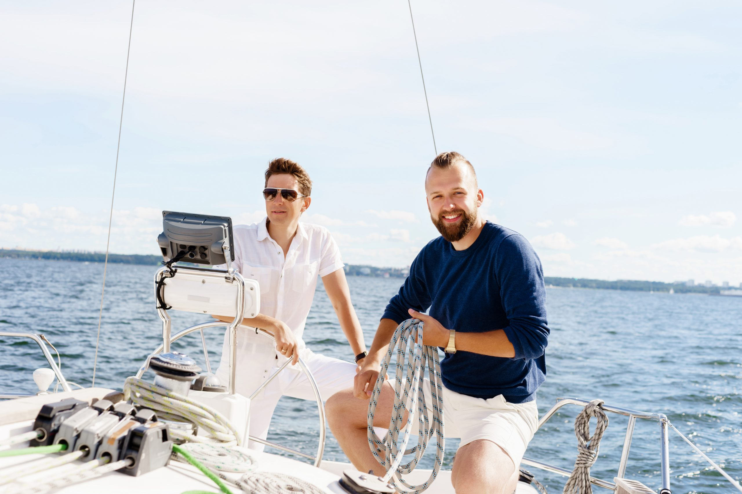 Two men stood on a boat with the ocean behind them