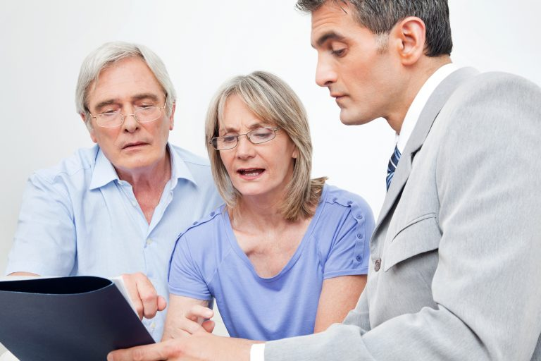 Elderly man and woman talking to younger man