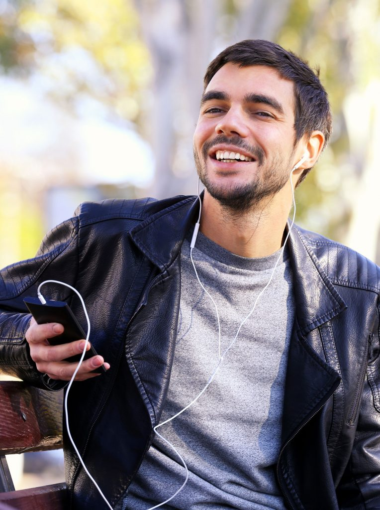 Man listening to music on a park bench